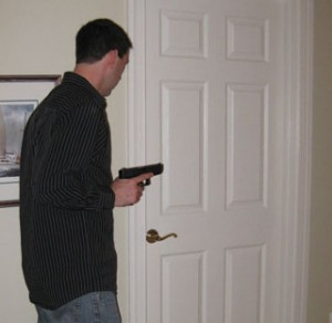 Standing to the left of the door, with the gun close to his body, the author prepares to push open the door and quickly take a step back to his original position.