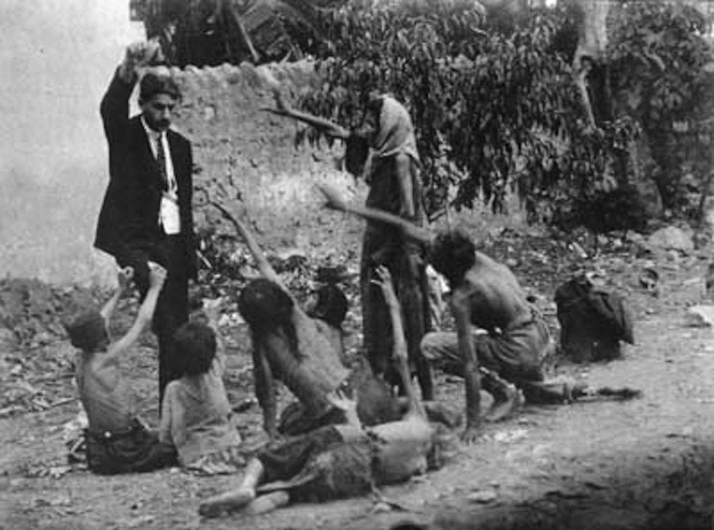 Turkish official teasing starved Armenian children by showing bread during the Armenian Genocide, 1915
