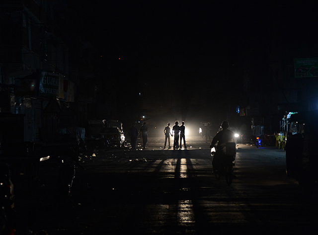 This picture taken on February 24, 2013 shows Pakistani youth crossing a street during a nationwide power blackout in Karachi. Pakistan was hit by a nationwide blackout for more than two hours after the breakdown of a major plant caused power stations to stop working across the country, officials said on February 25. AFP PHOTO/Asif HASSAN